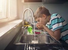 Jongen drinkt water van de kraan