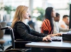 Meisje in rolstoel maakt gebruik van PC