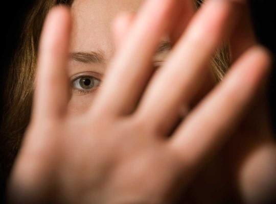 Vrouw houdt handen voor het gezicht